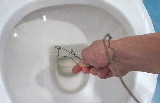 Удаление засора унитаза с помощью проволоки