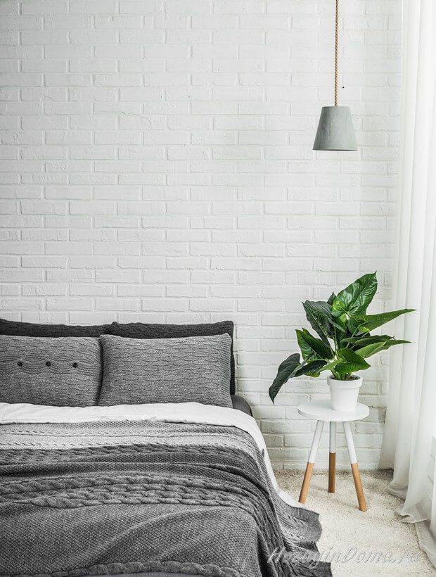 Спальня со стеной из белого кирпича